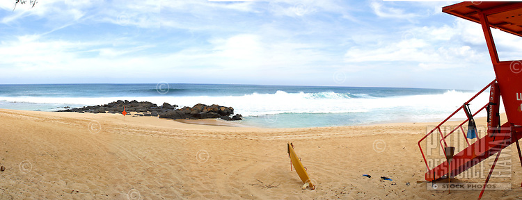 Wide angle panorama of rock piles beach with old fashioned orange lifeguard stand.