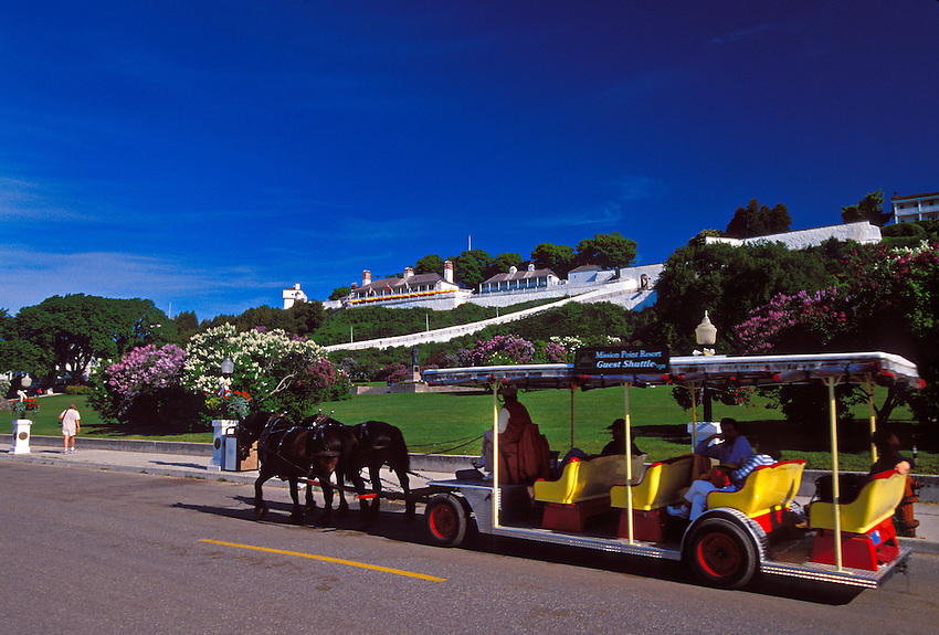 A HORSE-DRAWN SHUTTLE FOR THE MISSION POINT RESORT AT MACKINAC ISLAND, MICHIGAN WITH FORT MACKINAC IN BACKGROUND.