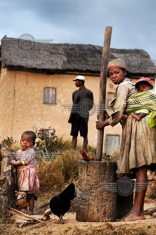 a woman, with a baby strapped to her back, pounds corn outside her home in a small highland village.
