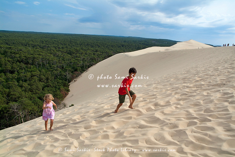 Boy and girl climbing the Great Dune of Pyla, Europe's tallest sand dune, Arcachon Bay, France.