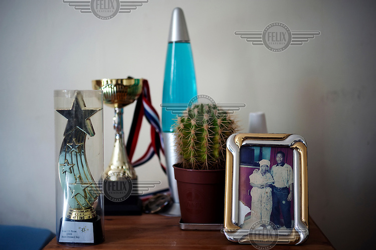 A photograph of Antonio's father Manuel and grandmother on a table at a house in Leeds, along with a martial arts medal and a trophy from a high school prom. Manuel committed suicide to prevent his son from being deported back to Angola.