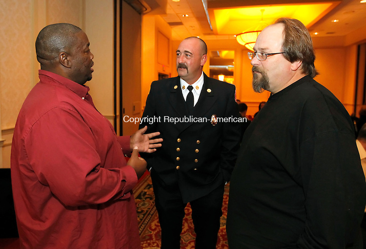 Waterbury, CT-01 November 2012-110112CM04-  Randall Baker, left of Danbury chats with Waterbury Firefighter Deputy Chief, Mike Lawrence, center, and Ed Clini of North Haven during a Waterbury Fire Department awards dinner Thursday night at the CoCo Key Resort.  Baker, who was in a car accident on Interstate 84 in Waterbury, was saved from his burning car by Lawrence and Clini.  Christopher Massa Republican-American