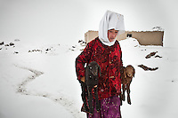 A reklative of the late Khan carries a pair of lambs to be reunited with their mothers at milking time. For the rest of the day, the vulnerable babies are kept warm inside the dung fire heated huts. Outside in the bitter cold they would have no chance of survival..Kyzyl Qorum, campment of the former deceased Khan, Abdul Rashid Khan.
