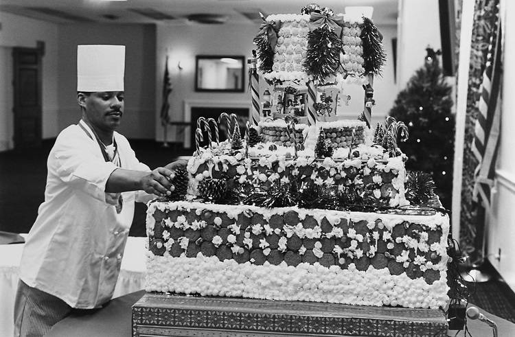 Larry Poteat puts the finishing touches on his gingerbread carousel cake at a Rayburn House Office Building, on Dec. 23, 1993. (Photo by Chris Martin/CQ Roll Call via Getty Images)
