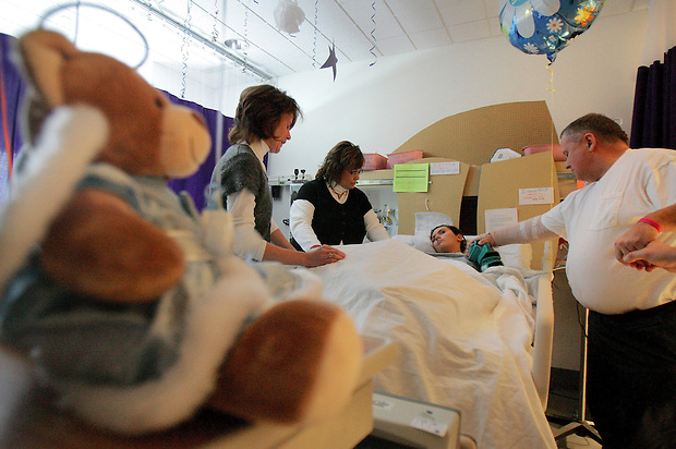 """Grant her your strength, dear Lord,"" prays family friend Lori Anderson, left, with Barb and Mike Cassler over Elizabeth's bed at Blank Children's Hospital.  Stuffed animals, balloons and streamers adorn her room, a space in which her parents only allow positive words and comforting imagery."