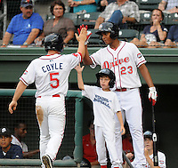 Infielder Sean Coyle (5) is congratulated by Xander Bogaerts (23) of the Greenville Drive and a young batboy after scoring a run in a game against the Lexington Legends on August 5, 2011, at Fluor Field at the West End in Greenville, South Carolina. (Tom Priddy/Four Seam Images)