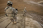 Spc. Christopher Kuntor, 26, of Accra, Ghana, and Sgt. Jeremiah Cummings, 28, of Charlotte, N.C.,  two soldiers with Company D, 2nd Battalion, 2nd Infantry Regiment, check under a bridge for Taliban bombs in Maiwand district, Kandahar province, Afghanistan. Jan. 9, 2009. DREW BROWN/STARS AND STRIPES
