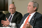 United States Secretary of the Treasury Henry Paulson, left, looks on as U.S. President George W. Bush delivers remarks at a meeting on financial literacy at the White House on April 25, 2007. <br /> Credit: Dennis Brack / Pool via CNP