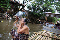 A woman washes herself in the Ciliwung River, a waterway that has been described as one of the most polluted rivers in the world. The river often floods, breaking its banks sending its polluted water into the nearby communities.