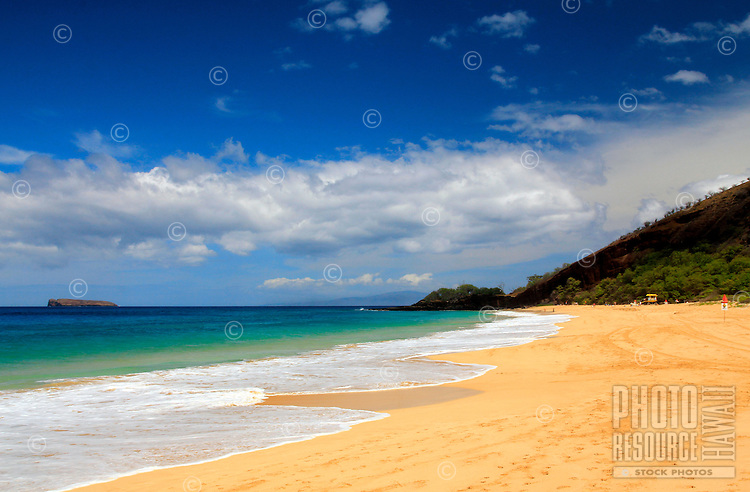 "A sunny day at Makena Beach (a.k.a. ""Big Beach"") on Maui, with clear blue water and Molokini Crater in the distance."