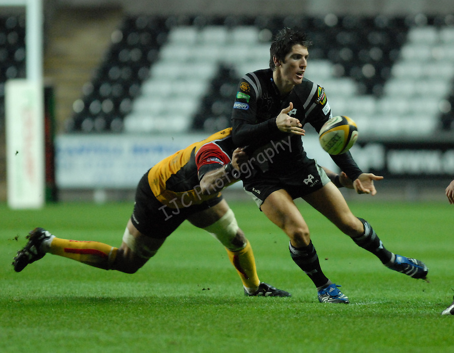 James Hook gets the ball wide, while under pressure from Richard Parks. Swansea Neath Ospreys Vs Newport Gwent Dragons, Magners league, Liberty Stadium © IJC Photography. Photographer Ian Cook