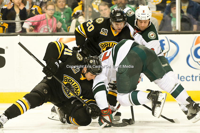 March 17, 2014 - Boston, Massachusetts , U.S. - Boston Bruins center Gregory Campbell (11) and Minnesota Wild left wing Erik Haula (56) fight for the puck during the NHL game between the Minnesota Wild and the Boston Bruins held at TD Garden in Boston Massachusetts. The Bruins defeated the Wild 4-1 at the end of regulation.  Eric Canha/CSM