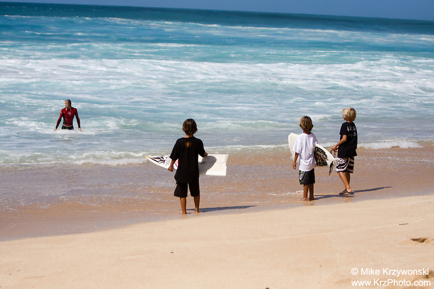Young boys on the beach retrieve broken surfboard for pro surfer competing in the Pipe Masters surfing contest, Banzai Pipeline, North Shore, Oahu, Hawaii