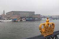 The Swedish Royal Palace in the Gamla Stan, Old Town. A crown on the bridge to Skeppsholmen in the foreground. In foggy winter weather. Stockholm. Sweden, Europe.