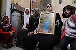 """The mother and other family members of a Palestinian man Abdelrahman Shaludi, who killed a baby and injured six others in Jerusalem after he rammed his vehicle into pedestrians near a tramway in what Israeli police called a """"hit-and-run terror attack"""", hold his portrait at their family home in the east Jerusalem neighbourhood of Silwan on October 23, 2014. Shaludi died of his injuries after he was shot and wounded by police as he tried to flee the scene late the previous evening. Photo by Muammar Awad"""