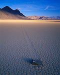 Death Valley National Park, CA<br /> Tiled patterns of the Racetrack playa - a dried lake bed with path of windblown 'moving' rock approaching the morning sun