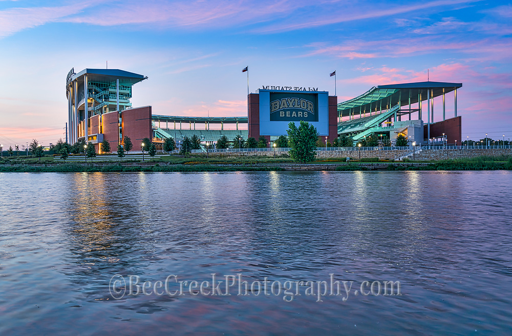 Capture this around dusk right after the sun went down over the McLane Stadium where the Baylor Bears play in Waco Texas as twilight was begining.  We like all the colors at twilight in the  sky with the nice colorful pink clouds still showing as the stadium lights up across the waters of the Brazos River near the University of Baylor. This is a relativity new stadium for Baylor University and it is really a pretty stadium sitting right along IH35 or the Jack Kultgen freeway .The highway through Waco is called the Jack Kultgen Freeway named after a civic leader and philanthropist who did a lot of work for charities in Waco for six decades. The new stay bridge along side has made access here a lot easier and has now become a iconic site on it own because of the wonderful led lights on the bridge at night.