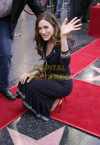 SARAH JESSICA PARKER.At the Star Ceremony on the Hollywood Walk of Fame Honoring Matthew Broderick and Nathan Lane, Hollywood, California..January 9th, 2006.Photo: William Scott/AdMedia/Capital Pictures.Ref: WS/ADM.full length blue dress kneeling crouching hand waving gesture.www.capitalpictures.com.sales@capitalpictures.com.© Capital Pictures.