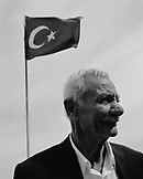 TURKEY, Istanbul, mature fisherman smiling with Turkish flag in the background