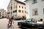 A bike rider passes classic cars as they pass through the small Swiss town of Punt-Chamues in the Graubunden region headed towards St. Mortiz, Switzerland during the British Class Car Meeting, an annual event featuring: Rolls-Royce, Bentley, Aston Martin & Lagonda, Jaguar & Daimler, and Austin-Healey & Healey and a limited number of pre-1960 British cars