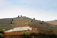 The chapel from below with the Chapelle vineyard and a sign painted black on white Ermitage M Chapoutier. The Hermitage vineyards on the hill behind the city Tain-l'Hermitage, on the steep sloping hill, stone terraced. Sometimes spelled Ermitage. Tain l'Hermitage, Drome, Drôme, France, Europe