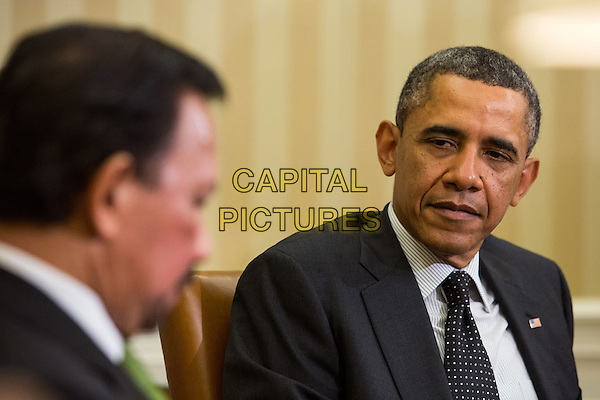 United States President Barack Obama (R) sits with Sultan Haji Hassanal Bolkiah of Brunei, at the end of a bilateral meeting in the Oval Office at the White House on March 12, 2013 in Washington, DC. The two discussed strategic and economic issues in advance of October's East Asia summit and US-ASEAN summit in Brunei.  .headshot portrait suit black white stripe shirt.CAP/ADM/CNP/DA.©Drew Angerer/CNP/AdMedia/Capital Pictures.