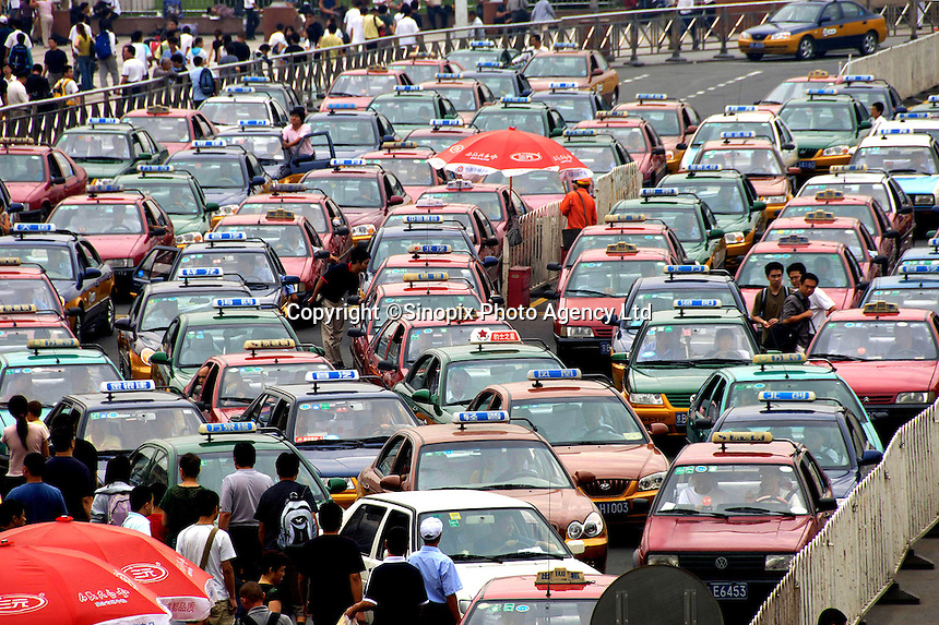 Taxis wait while a migrant worker who threatens to jump from the top of an overpass bridge while demanding the government help him get his unpaid salaries in front of Beijing raiway station. .22 Aug 2006