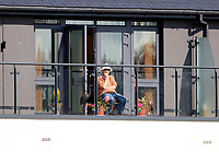 A spectator looks on from their luxury apartment overlooking the St Lawrence ground during the friendly game between Kent CCC and Surrey at the St Lawrence Ground, Canterbury, on Thursday Apr 5, 2018