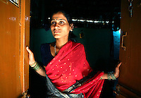 "Kasvva Haragan, 28, waits for a customer at her brothel door in Gokak, India.  Her  parents dedicated her as a Devadasi at the age 12 and to avoid the legal ramifications of the Devadasi Protection Act, had a ceremony at home. She now lives and works in a brothel with 2 other women and support her parents, two sisters and a brother.  She also gives 50% of her earnings to the brothel owner. ""Who would want to marry me? I'm a Devadasi,"" she says when asked if she'd like to marry a man. Haragan is illiterate as she worked in the sugar cane fields as a child rather than going to school and therefore has few other options to make an income. ."