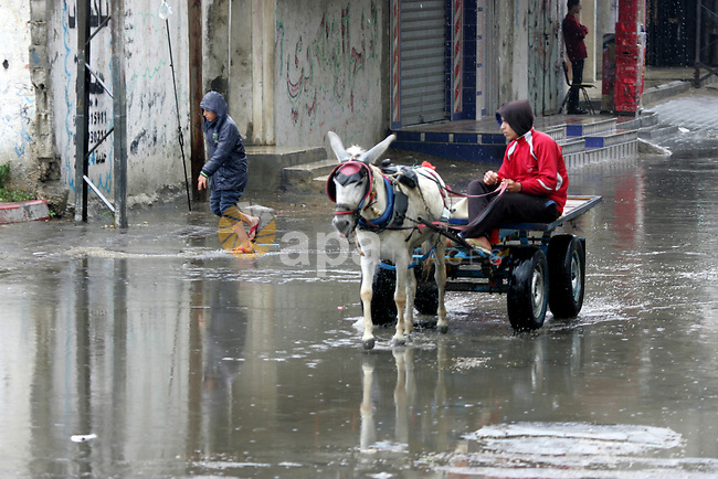 Palestinians walk in a flooded street during a rainy day, in Rafah in the southern Gaza strip on March 28, 2016. Photo by Abed Rahim Khatib