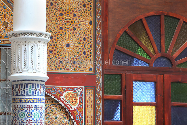 Painted wooden panels, a stained glass door and a zellige tile decorated pillar in the central courtyard area, in a typical Tetouan riad, a traditional muslim house built around a courtyard, built in Moorish style with strong Andalusian influences, next to the Great Mosque or Jamaa el Kebir in the Medina or old town of Tetouan, on the slopes of Jbel Dersa in the Rif mountains of Northern Morocco. Tetouan was of particular importance in the Islamic period from the 8th century, when it served as the main point of contact between Morocco and Andalusia. After the Reconquest, the town was rebuilt by Andalusian refugees who had been expelled by the Spanish. The medina of Tetouan dates to the 16th century and was declared a UNESCO World Heritage Site in 1997. Picture by Manuel Cohen