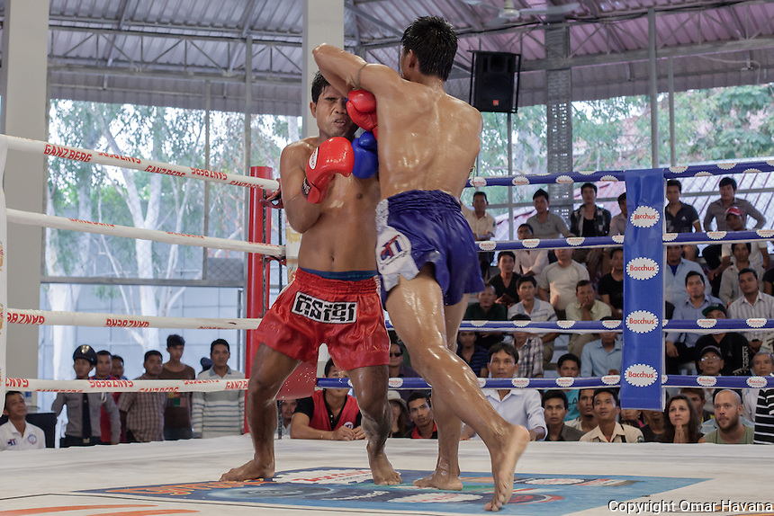 SIEM REAP, CAMBODIA. A Kun Khmer fighter elbows his opponent during a fight in the Siem Reap arena in Cambodia. Kun Khmer tends to utilise more elbows than that of other regions. Most Cambodian boxers come from a poor background and compete to earn money to feed their families and themselves. They average from age 14 to 25. Top Kun Khmer fighters can have as many as 300 fights in their careers. Pradal Serey or Kun Khmer -free fighting- is an unarmed martial art from Cambodia. Compared to other forms of Southeast Asian kickboxing, Kun Khmer emphasises more elusive and shifty fighting stances. The Cambodian style tends to utilise more elbows than that of other regions. Evidence shows that a style resembling pradal serey existed in the 9th century, leading the Khmer to believe all Southeast Asian forms of kickboxing started with the early Mon-Khmer people. They maintain that Pradal Serey has influenced much of the basis of Muay Thai. During the Khmer Rouge genocide, traditional martial arts were banned and many boxers were executed or worked to death, which nearly caused the death of pradal serey. Nowadays, Kun Khmer is making a strong comeback in Cambodia, with fighters attempting to market their style of boxing at the same caliber of Muay Thai. Photography: ©Omar Havana