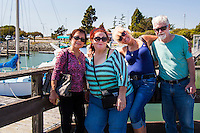 Four friends pose for photographs on the public observation deck at the San Leandro Marina.