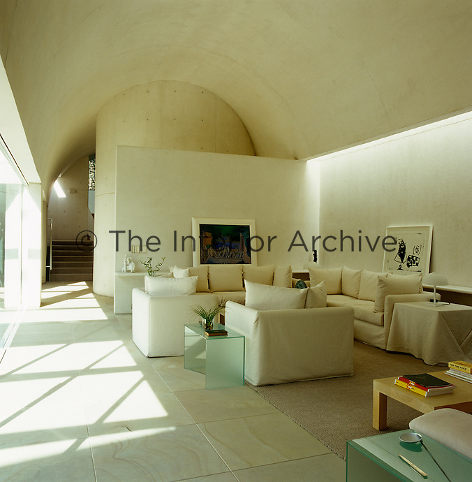 The living room has a high curved ceiling and is furnished with cream sofas and armchairs