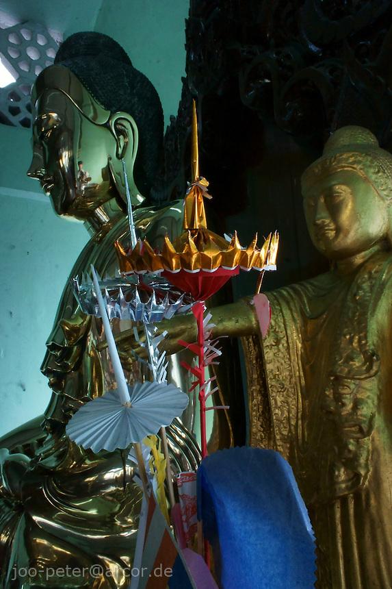 golden buddha sculpture in a shrine in Sula Paya pagoda complex, center of Yangon, Myanmar, 2011
