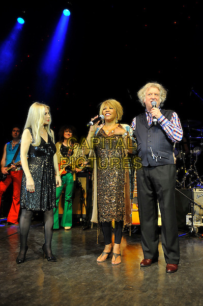 Singer / songwriter Lynsey De Paul has died at the age 64 following suspected brain haemorrhage. She represented the UK in the 1977 Eurovision Song Contest and was best known for her hits Sugar Me and Won't Somebody Dance With Me.<br /> STOCK PHOTO: Lynsey de Paul, Linda Lewis and Noddy Holder<br /> performing for Marc Bolan's 35th anniversary concert in aid of the PRS for Music Members Benevolent Fund, Shepherd's Bush Empire, London, England. <br /> 15th September 2012<br /> on stage in concert live gig performance performing music full length black dress waistcoat singing check shirt blue gold<br /> CAP/MAR<br /> &copy; Martin Harris/Capital Pictures