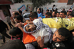 """Mourners carry the body of Mohammed Abu Saada, a 26-year-old Palestinian man who was reportedly killed in clashes with the Israeli army along the Gaza border, during his funeral in the Nuseirat refugee camp in the central Gaza Strip on November 19, 2016. """"Mohammed Abu Saada died after being shot in the chest by Israeli soldiers in clashes east of the Al-Bureij camp,"""" the health ministry in the Palestinian enclave on November 18. The Israeli army confirmed clashes in the area, which is in central Gaza, but could not immediately provide details. Photo by Ashraf Amra"""