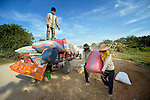 Workers load rice on a trailer in the village of Dong in northern Cambodia.