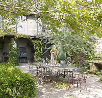An outdoor dining area, sheltered in a courtyard between the barns, surrounded by foliage growing up columns, box hedges and a tree canopy