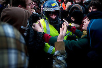 A policeman is protected by a protester after being cut off after a baton charge during a student demonstration in Westminster, central London on the day the government passed a bill to increase university tuition fees.