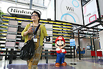 June 29, 2010 - Tokyo, Japan - A visitor of Panasonic Center Tokyo is pictured with mascot Nintendo's popular game character Super-Mario on June 29, 2010.