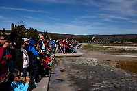 Tourists watch from a boardwalk as Old Faithful erupts in Yellowstone National Park, Wyoming on Tuesday, May 23, 2017. (Photo by James Brosher)