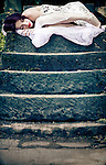 Image of a sleeping young woman on the top of a set of stone steps in a peaceful garden setting