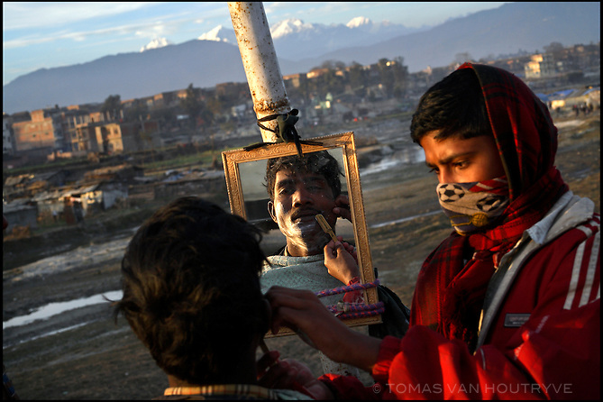 A boy shaves a man at a roadside barber stand near slum housing for recent migrants from rural areas on the outskirts of Kathmandu, on 7 January, 2006. The decade long conflict between Maoists and the Hindu monarchy has driven thousands of people out of the rural areas and into the city.<br />