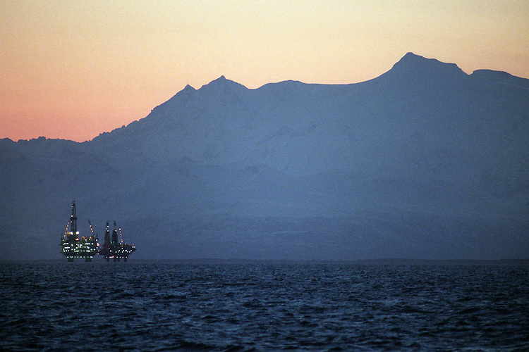 Oil and natural gas platforms stand in Cook Inlet, offshore from Nikiski, Alaska as night falls. Mount Spurr, an active volcano in the Alaska Range, dominates the horizon.