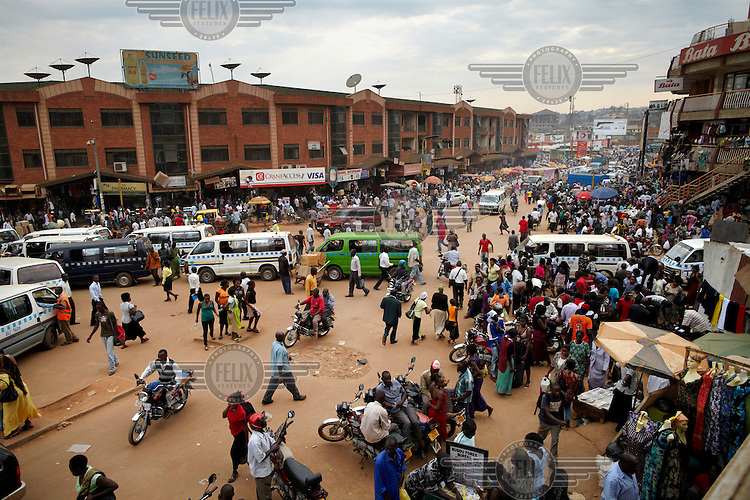 Pedestrians and mini buses crowd a busy intersection in the centre of Kampala.