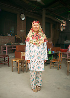 China / Henan Province / Luoyang / Mapo village / 24.6.2013 / Ding Xiangzhen, the Imam's daughter and Lan's aunt, poses for a portrait in the yard of her house, where she organizes a Koranic school during the summer.<br />