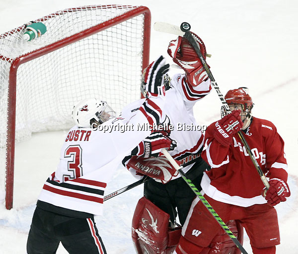 Wisconsin's Mark Zengerle uses a high stick to knock the puck into the UNO net during the first period. After a video review the goal was disallowed. Defending for UNO are Andrej Sustr and goalie John Faulkner. No. 16 UNO beat No. 7 Wisconsin 4-3 Saturday night at Qwest Center Omaha. (Photo by Michelle Bishop)
