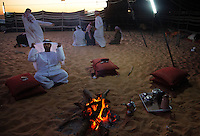 Evening prayers end and the Al Mansori family gathers at the campfire. Modern symbols of cigarettes and cell phones contrast the traditional elements of Bedouin culture--tents, teapots and a campfire.<br /> They are from outside Abu Dhabi, but  walked with their camels 50 miles even though they are wealthy, they did not want to risk transport in trucks for their precious animals.  The patriarch won a car today and another camel got a first place (up to a million DRH).<br /> Men sleep at in tents in the desert and are hospitable to all with ample food, a part of Bedouin culture.