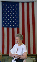 A woman stands in front of an American flag in the historical museum at the Knox County Fair in Mt. Vernon, Ohio.<br />